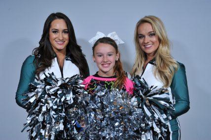 Two Philadelphia Eagles Cheerleaders meet a fan at the stadium.