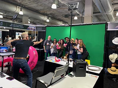 Photographer Mike Gatty poses participants at a Las Vegas green screen photo booth