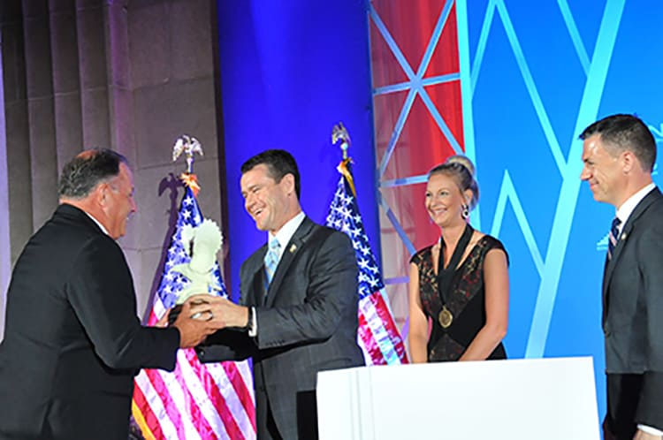 An award winner accepts an award on stage at this national convention.